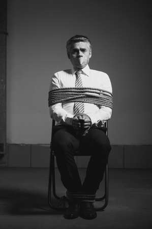 duct tape: Kidnapped businessman. Black and white image of tied up businessman sitting at the chair and looking at camera