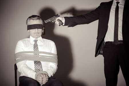 Kidnapper and victim. Tied up businessman sitting at the chair while young man in formalwear aiming him with gun photo