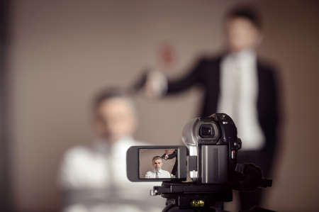Crime scene.  Close-up of home video camera shooting a man in formalwear aiming a tied-up businessman photo