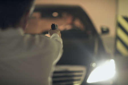 Killer with gun. Rear view of men with handgun aiming the car driver photo