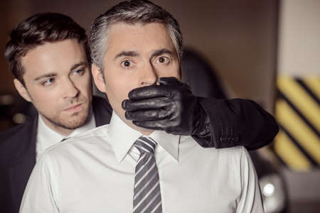 Kidnapping. Aggressive young men covering businessman mouth with his hand in glove photo