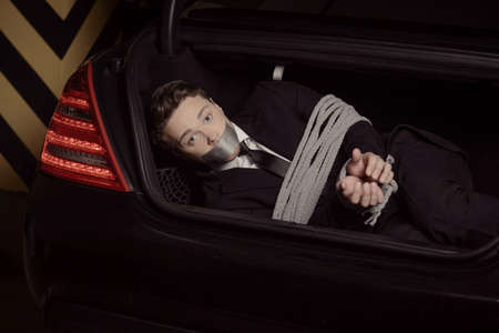 Kidnapped businessman. Tied up young men lying in the car trunk and looking at camera photo