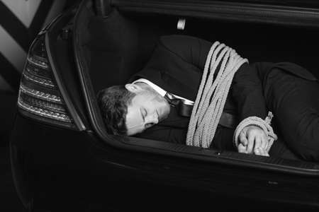 duct tape: Kidnapped businessman. Black And White image of tied up young men lying in the car trunk Stock Photo