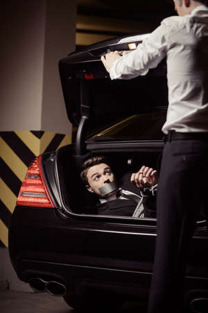 kidnapping: Kidnapped businessman. Tied up young man lying in the car trunk and looking at kidnapper