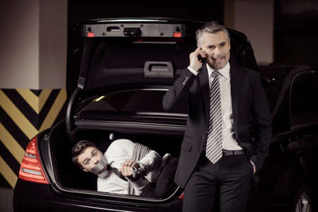 tied down: Kidnapped man. Tied up businessman lying in the car trunk and looking at camera while kidnapper talking at mobile phone Stock Photo
