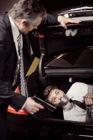 car trunk: Kidnapped man. Tied up businessman lying in the car trunk and looking at kidnapper holding a gun in his hand Stock Photo