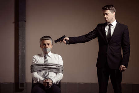 Kidnapper and victim. Tied up businessman sitting at the chair and looking at camera while young man in formalwear aiming him with gun photo