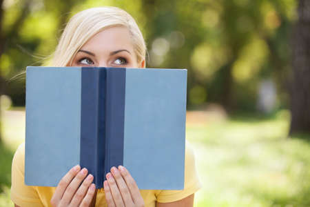 woman reading book: Beautiful young women holding book in front of her face and looking out of it while relaxing in park Stock Photo
