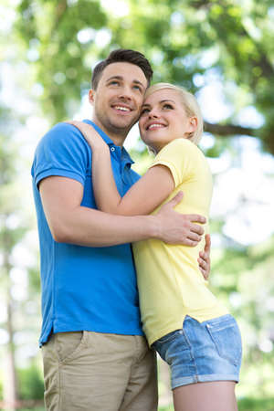 toothy smile: Low angle view of young loving couple hugging and looking away Stock Photo