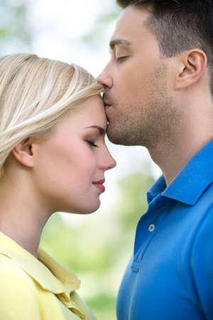 enamorados besandose: Vista lateral de un hombre apuesto joven besa a su novia en el parque