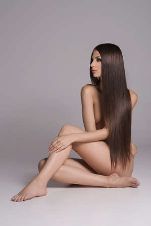 Long hair beauty. Attractive naked women with beautiful hair sitting on the floor and looking away while isolated on white photo