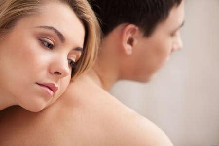 hombres sin camisa: Dificultades de relación. Mujer deprimida joven que se inclina a su novio de vuelta y mirando a otro lado Foto de archivo