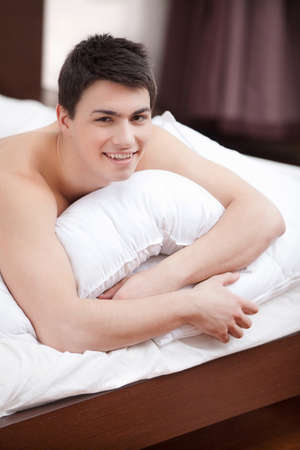 Waking up. Handsome young man lying on bed and smiling at camera photo