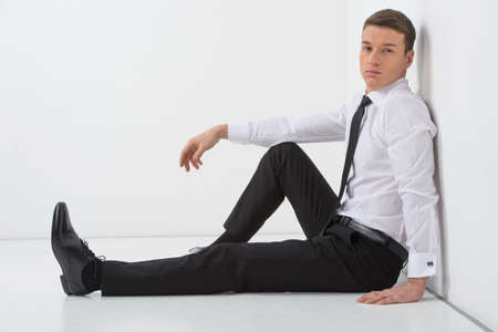 Handsome man sitting on the white floor. Wearing modern business suite photo