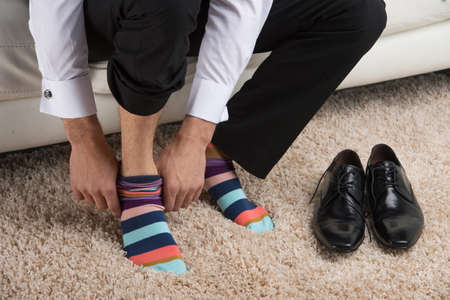 Close up of a man wearing colorful sock under classical business suite. Idea of being different