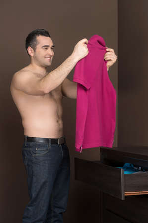 choosing clothes: Man choosing clothes. Cheerful middle-aged man holding a T-Shirt and smiling