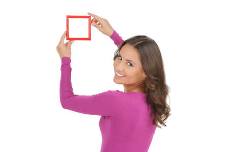 over the shoulder view: Women with picture frame. Rear view of beautiful young women holding a picture frame and smiling while isolated on white