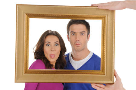 making a face: Funny people in frame. Beautiful young couple looking through a picture frame and grimacing while isolated on white