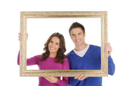 Happy couple in frame. Beautiful young couple looking through a picture frame and smiling while isolated on white photo