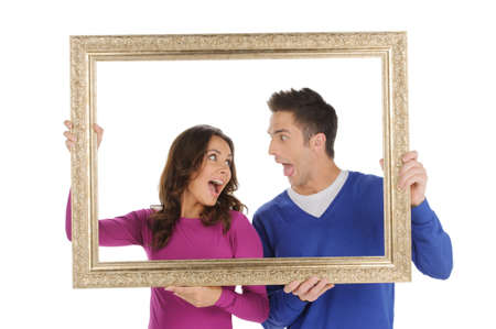 Couple in frame. Beautiful young couple holding a picture frame and grimacing while isolated on white