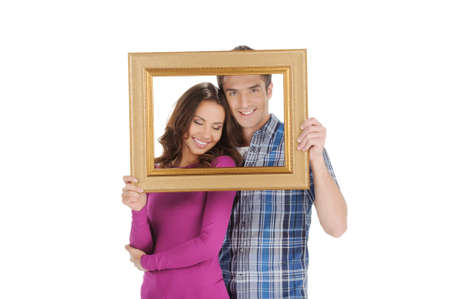 Loving couple in picture frame. Beautiful young couple looking through a picture frame and smiling while isolated on white photo