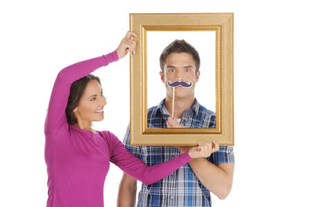 Loving couple having fun. Beautiful young woman holding a picture frame in front of her boyfriend face and smiling while isolated on white photo
