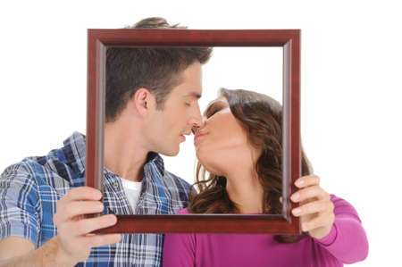 Kissing in a picture frame. Beautiful young couple holding a picture in front of their faces and kissing while isolated on white photo
