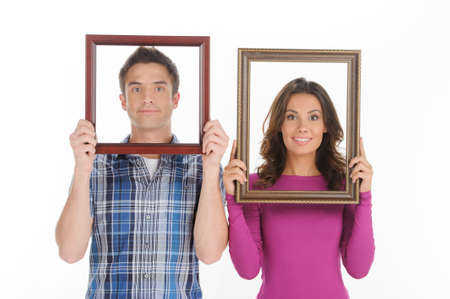 Couple with picture frames. Beautiful young couple looking through a picture frames and smiling while isolated on white photo