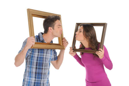 kissing lips: Couple with picture frames. Beautiful young couple holding a picture frames in their hands and trying to kiss each other while isolated on white