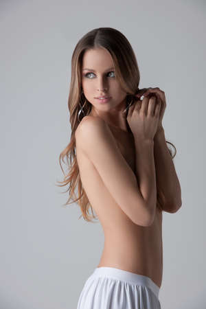 woman nude standing: nude beauty. Attractive young woman standing topless and covering breasts with hands while isolated on white