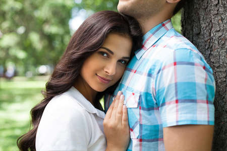 young couple smiling: Loving couple. Beautiful young woman leaning to her boyfriend and smiling