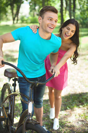 toothy smile: Couple in spring park. Cheerful young couple with bicycle having fun in park