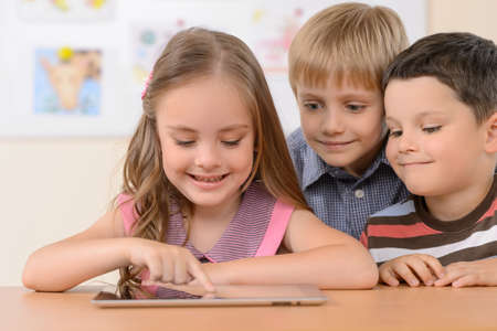 Children with digital tablet. Cheerful children looking at the digital tablet and smiling photo