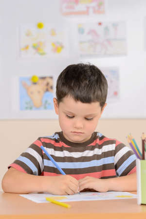 preadolescence: Diligent pupil. Confident schoolboy drawing while sitting in classroom