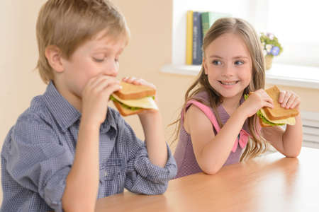 children eating: Children eating sandwiches. Two cheerful children eating sandwiches and smiling Stock Photo