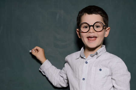Happy learner. Cheerful little schoolboy in glasses standing near the blackboard and smiling photo