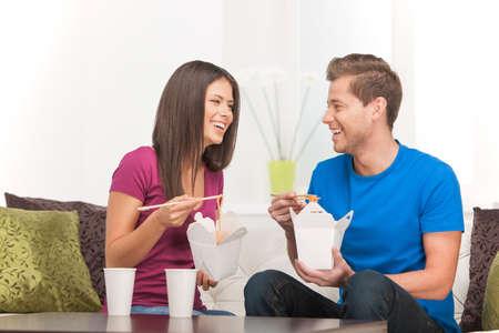 pareja comiendo: Comer comida asiática. Hermosa joven de comer comida asiática de los envases de alimentos y sonriente Foto de archivo