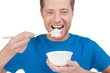 Man eating rice. Portrait of cheerful young man eating rice from the bowl while standing isolated on white photo