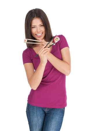 Woman with sushi. Beautiful mixed race woman holding sushi by chopsticks and smiling at camera while standing isolated on white photo