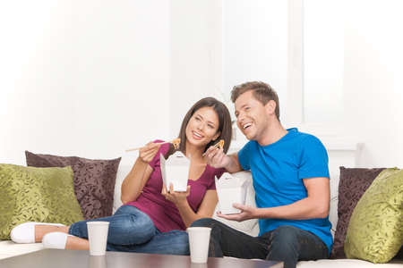 couple on couch: Eating Asian food. Beautiful couple eating Asian food from food containers and looking away while sitting on the couch