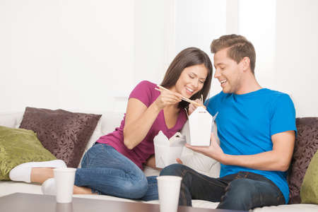 Couple eating Asian food. Beautiful couple eating Asian food from food containers while sitting close to each other on the couch photo