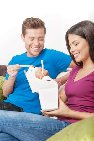 Couple eating Asian food. Cheerful young couple eating Asian food from food containers while sitting close to each other on the couch photo