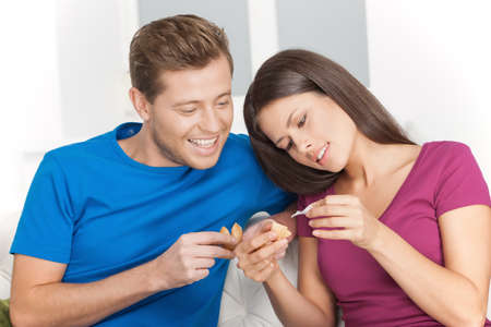 Fortune cookie. Cheerful young couple checking the fortune cookies while sitting close to each other on the couch photo