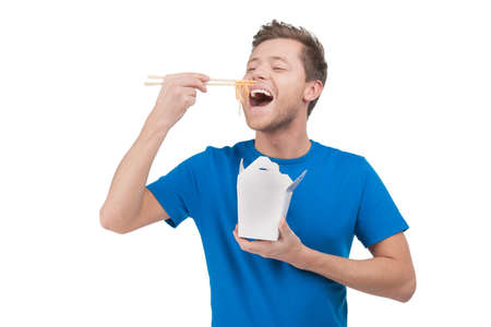 Man eating noodles. Cheerful young man eating rice from the food box while standing isolated on white photo