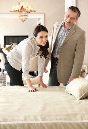Couple in furniture store. Cheerful middle-aged couple choosing furniture in store Stock Photo