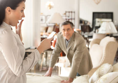 Shocked with a price. Shocked middle-aged woman holding a price while standing near her husband at the furniture store photo
