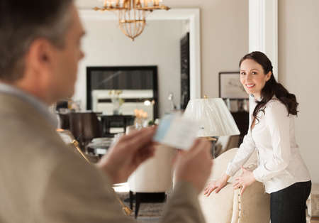 Thinking about a price. Thoughtful middle-aged man holding a price while standing near his wife at the furniture store photo