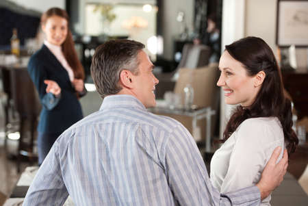 Mature couple in furniture store. Cheerful middle-aged couple making decision about buying furniture while female sales clerk waiting on background photo