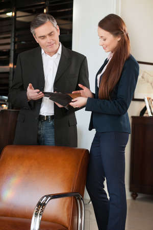 furniture store: Man in furniture store. Confident mature man talking with sales clerk and looking at the brochure at the furniture store