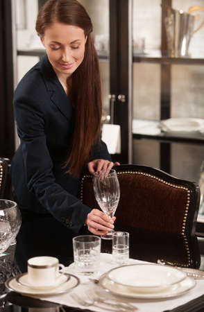 Woman serving table. Beautiful young woman in formalwear serving a table Stock Photo - 23410851